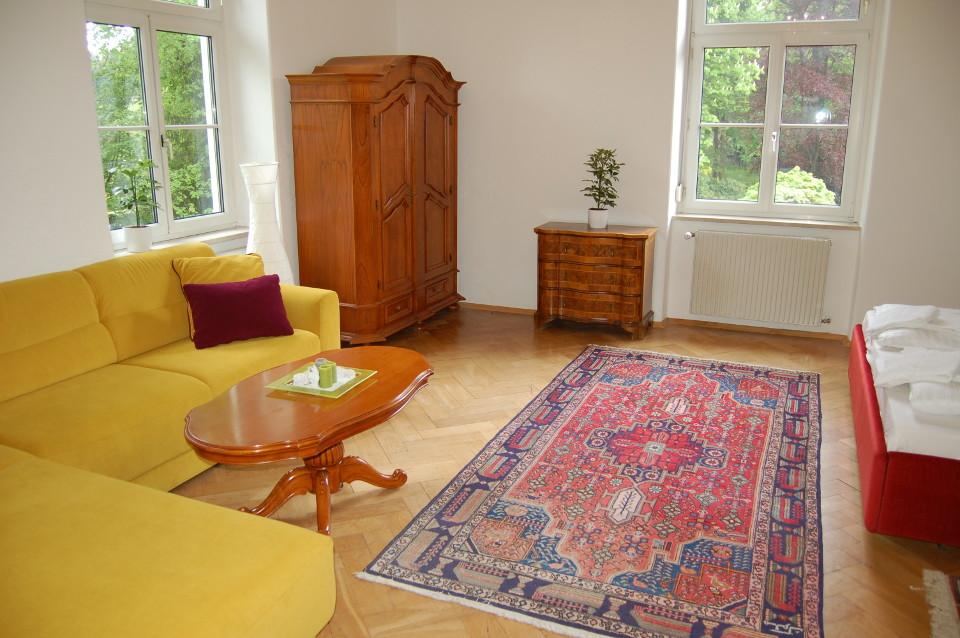 Großzügiges Zimmer mit Sitzecke und Blick ins Grüne