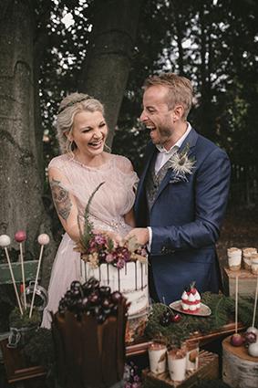 Das Brautpaar schneidet die Hochzeitstorte beim Sweet Table im Park an.