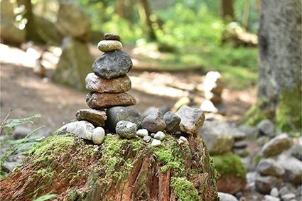 Meditieren beim Steine balancieren nach dem Seminar im Park des Glögglhofs